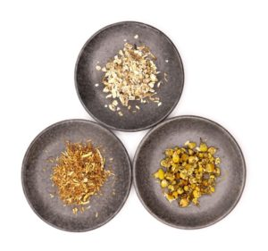 overhead view of loose bitter herbs gentian, chamomile and orange peel